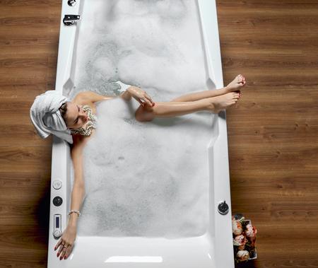 Mujer de moda de lujo con toalla grande grande en el spa de spa de limpieza que miente en el baño de baño que sopla en la habitación de espacio grande Foto de archivo - 87181766