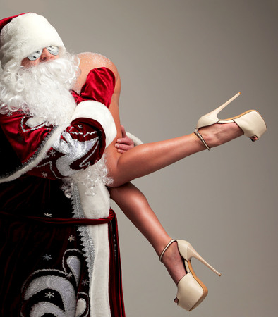 New year 2018 christmas concept. Bad santa claus in snow flakes sunglasses honding young sexy naked ass woman with long legs and high hills