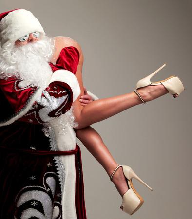 Nuevo año 2018 concepto de Navidad. Papá Noel malo en copos de nieve gafas de sol honding joven mujer sexy culo desnudo con piernas largas y altas colinas Foto de archivo