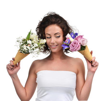 Woman comparing two bouquet of tulip gypsophila chrysanthemum iris flowers and roses in waffle cones close up portrait isolated on a white background