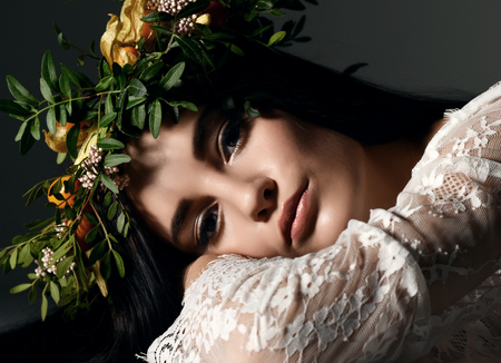 Beautiful portrait of young woman with wreath of flowers lying on a floor on dark background Stockfoto