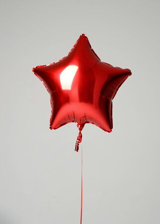 Single red big star metallic balloon object for birthday on a grey background