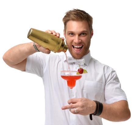 바텐더 남자 빨간색 마가리타 칵테일 딸기와 라임 준비하고있다. 큰 유리를 잡고 흰색 배경에 고립 된 황금 셰이 커에서 알코올을 따른다.