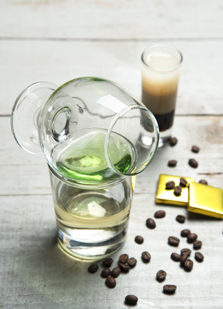 drunken: Alcohol green sambuca cocktail with coffee and chocolate on rustic wood background