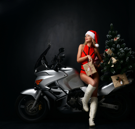 Portrait of sexy blonde woman in Christmas Santa costume sitting on motorcycle looking at the corner. Holidays New Year 2018 on dark background