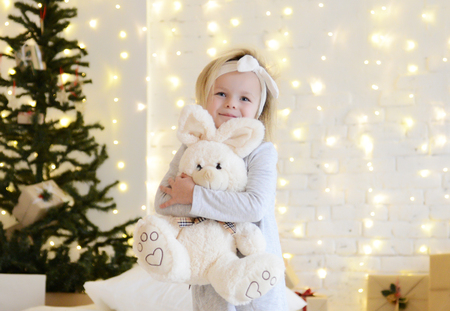 Young baby girl sitting dreaming near magical New year craft gifts by a Christmas tree on yellow magic lights background