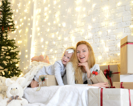 ittle: Young mother and her ittle daughters lying near magical New year gifts by a Christmas tree in cozy living room in winter on yellow magic light background
