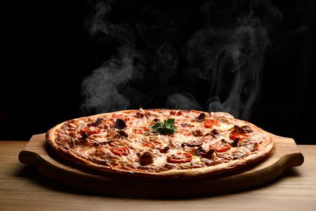 黒い背景にとろけるチーズ ベーコン トマト ハム パプリカ ホット大きなペパロニのピザおいしいピザ組成蒸気煙 写真素材