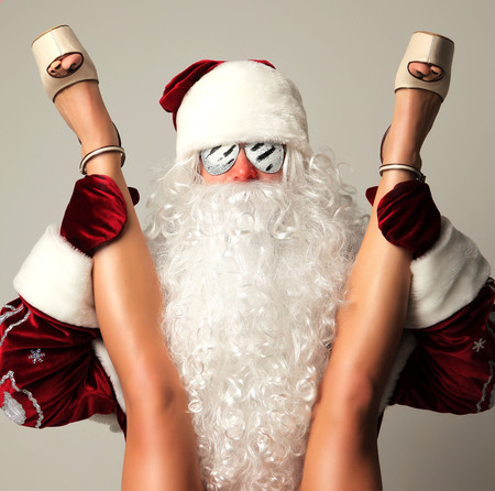 New year 2018 christmas concept. Bad santa claus in snow flakes sunglasses holding young sexy woman  long legs and high hills Archivio Fotografico