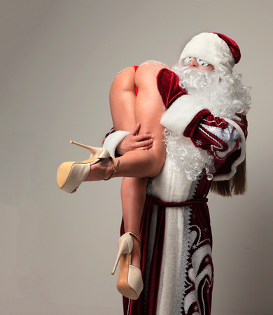 Bad santa claus in snow flakes sunglasses abduct young sexy naked ass woman with long legs and high hills. New year 2018 christmas concept