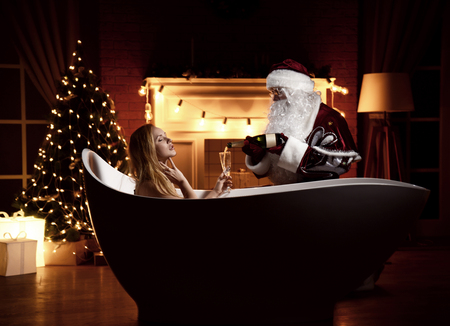 Young beautiful woman lying in bathtub over christmas tree interior background with retro light bulbs and santa claus pour champagne in glass. New year Holidays celebration concept