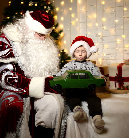 Santa Claus sitting with happy little cute baby boy kid near Christmas tree at home green retro car present Stock Photo
