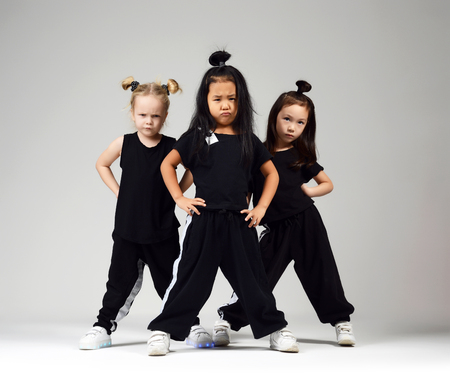 Group of three young girl kids hip hop dancers on gray background Archivio Fotografico
