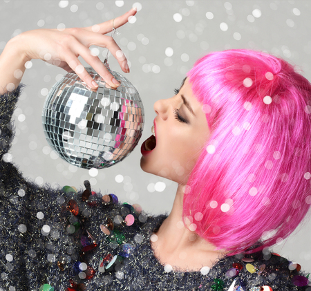 Portrait of young beautiful fashion woman in stylish pink wing bite christmas decoration disco ball on grey background under heavy snow Foto de archivo