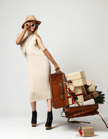 Beautiful woman traveler in hat with big open leather retro bag full of christmas present gifts and sunglasses looking at the corner on grey background. New year concept Stock Photo