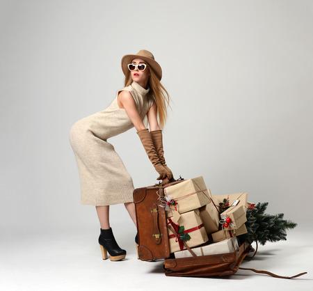 大きなオープン レザー クリスマス贈り物と灰色の背景にコーナーを見てのサングラスのレトロなバッグと帽子の美しい女性旅行者。新しい年の概念