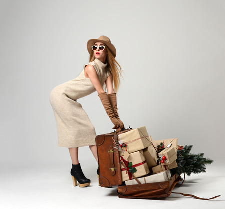 Beautiful woman traveler in hat with big open leather retro bag full of christmas present gifts and sunglasses looking at the corner on grey background. New year concept Foto de archivo