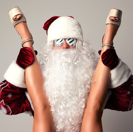 New year 2018 christmas concept. Bad santa claus in snow flakes sunglasses holding young sexy woman  long legs and high hills Stok Fotoğraf