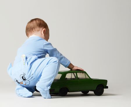 Infant child baby boy kid toddler sitting and playing with green retro car in light blue body cloth on gray background. Back rear view