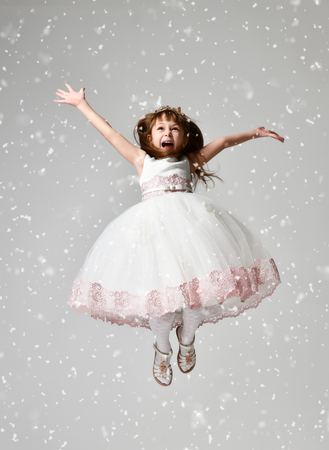 Young little girl jumping in the white communion winter dress under heavy snow with arms spread screaming yelling Stock Photo