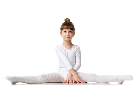 Young sport brunette girl do splits workout stretching exercises in white athletic body cloth over white background