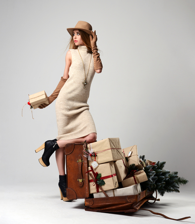 Beautiful woman traveler in hat with big open leather retro bag full of christmas present gifts looking at the cornet on grey background. New year concept Stock Photo