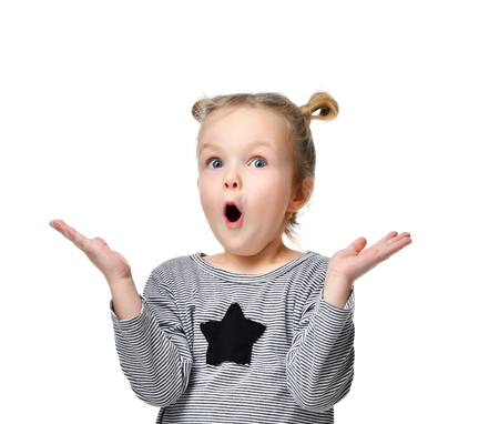 Young girl kid surprised and shocked with open mouth looking up hands spread isolated on a white background Foto de archivo