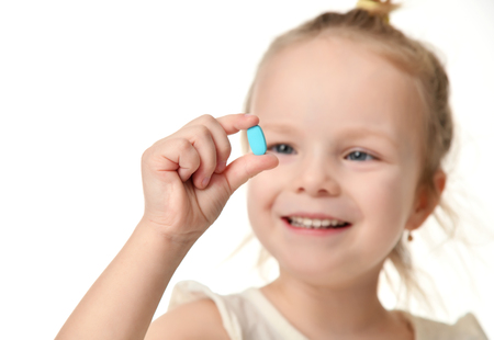 Young baby girl hold light blue headache  pill medicine tablet in small hand isolated on a white background Archivio Fotografico