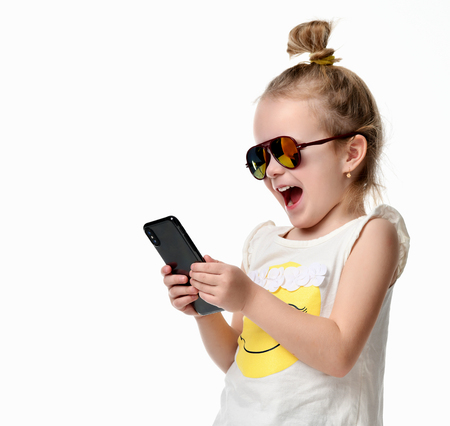 Pretty smiling young girl kid reading texting sms on the cellphone mobile with touch screen in sunglasses isolated on a white background Stok Fotoğraf - 93272947