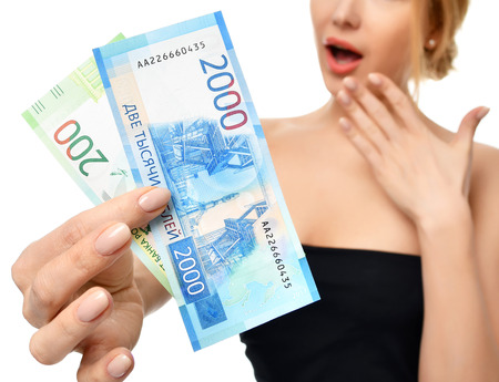 Young woman holding up cash money two thousand and hundred russian rubles notes in hand winner surprised isolated on a white background Stock Photo