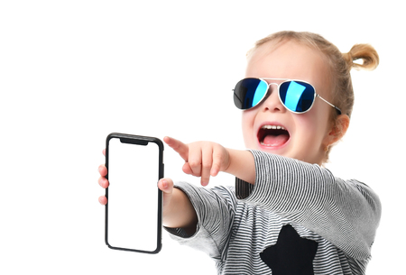 Little girl kid in blue aviator sunglasses showing blank screen of mobile phone shouting isolated over white background