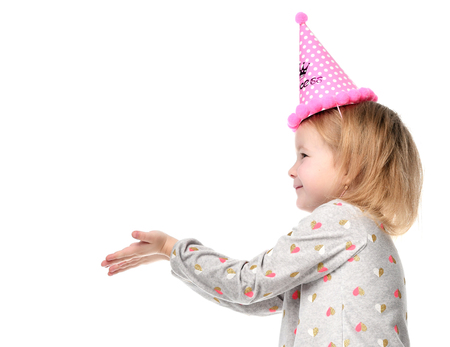 Young girl kid happy smiling and show hands with free text copy space in birthday party pink cap isolated on a white background
