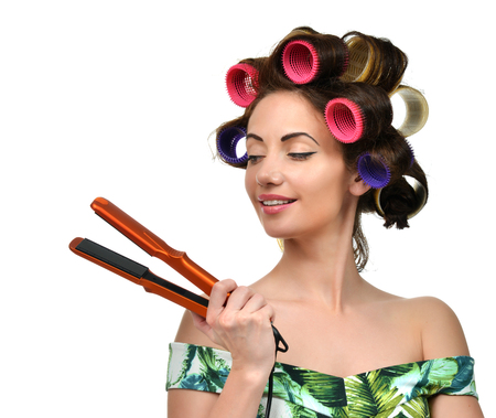 Woman with curlers hold hair curling ironing tool isolated on a white background