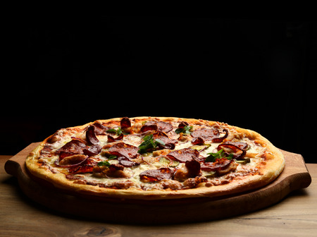 Pizza composition with melting cheese bacon tomatoes ham paprika on black background