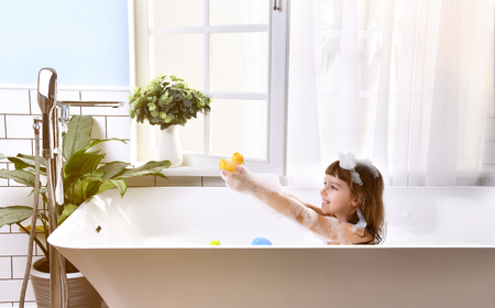 Happy little baby girl sitting in bath tub  in the bathroom. Portrait of baby bathing in a bath full of foam near window