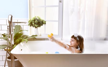 Pequeño bebé feliz que se sienta en tina de baño en el cuarto de baño. Retrato de bebé bañándose en un baño lleno de espuma cerca de la ventana