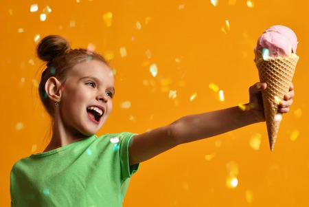Pretty baby girl kid rozdaje lody waniliowe w rożku wafle śmiejąc się i uśmiechając na żółtym tle