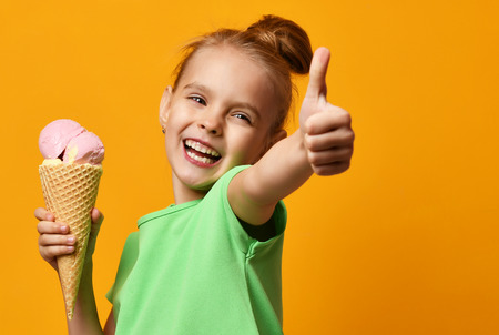 Pretty baby girl kid hold banana and strawberry ice cream in waffles cone on yellow background and show thumbs up sign with free text copy space Foto de archivo