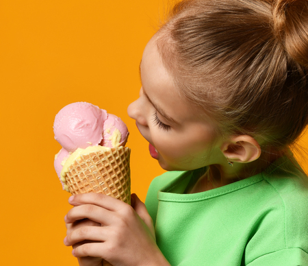 Pretty baby girl kid eating licking banana and strawberry ice cream in waffles cone on yellow background