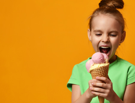Pretty baby girl kid eating licking banana and strawberry ice cream in waffles cone on yellow background with free text copy space