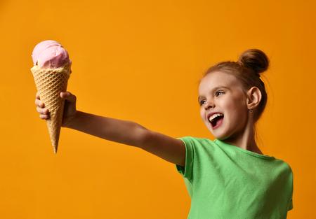 El bebé bonito de la niña sostiene el helado de fresa en cono de las galletas en el fondo amarillo que grita riendo con el espacio de la copia del texto libre Foto de archivo