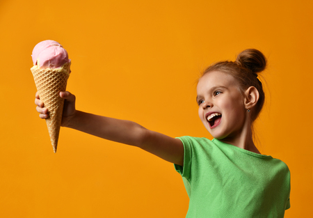 Pretty baby girl kid hold strawberry ice cream in waffles cone on yellow background screaming laughing with free text copy space