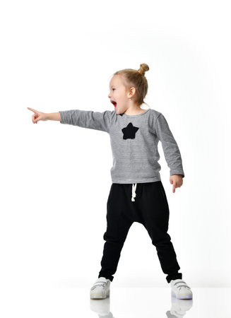 Young girl kid surprised yelling shouting pointing finger at the corner  isolated on a white background Stock Photo