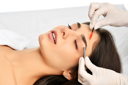 Beautician doing permanent eyebrows makeup. Closeup composition of beautiful woman face with thick brows In beauty salon. Preparation eyebrow for tattooing. Beauty procedure female face Stock fotó