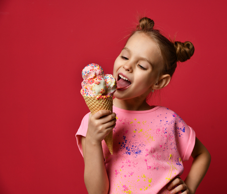Pretty baby girl kid eating licking big ice cream in waffles cone with raspberry happy laughing on red background Foto de archivo