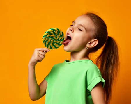 Happy young little child girl kid bite sweet lollypop candy on yellow background