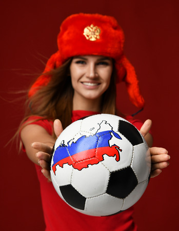 Russian style fan sport woman player in red uniform give soccer ball celebrating happy smiling on red background Stok Fotoğraf
