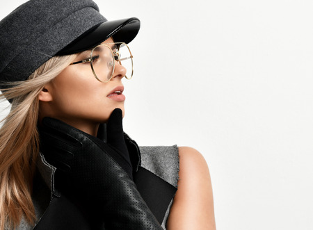 Young sexy brunette woman in grey peaked cap or beret in big clear gold sunglasses looking at the corner on grey background