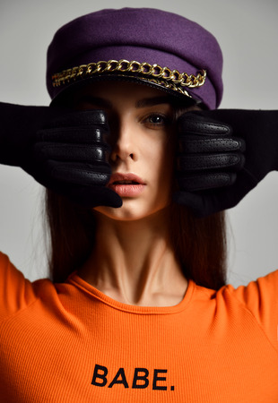 Portrait of young sexy brunette woman in purple peaked cap or beret with gold chain in leather gloves and orange shirt on grey background