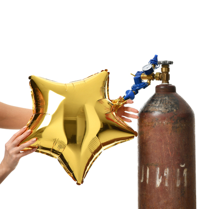 Hands inflate gold star balloon use Helium Tank with Economy Regulator Fill Valve for Latex Balloons isolated on white background 版權商用圖片